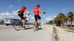 Cyclists share the road with car, ride with no hands Stock Footage