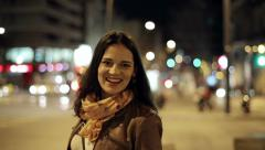 Portrait of smiling young woman in night city, steadicam shot Stock Footage