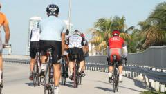 Cyclists going uphill on bridge on sunny day, palm trees & skyline in horizon. Stock Footage