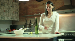 $Woman drinking white wine in her kitchen in the evening Stock Footage