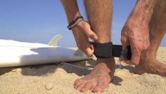 Surfer strapping a leash on his ankle - stock footage