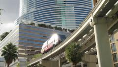 Electric Train goes by modern building Stock Footage