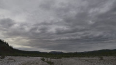 Yukon Dry Riverbed and Distant Hills Cloudy Stock Footage