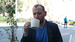 Unhappy man drinking coffee in the restaurant Stock Footage