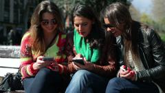 Three women sitting in the bench park and using smartphones Stock Footage