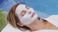 Stock Video Footage of Woman at spa lays by the pool with facial mask