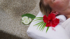 Woman at spa gets cucumbers put over eyes - stock footage