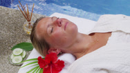 Stock Video Footage of Woman laying by pool at spa gets cucumbers on eyes