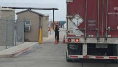 Security guard stops tractor trailer at gate Stock Footage