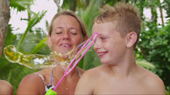 Mother and son making bubbles together Stock Footage