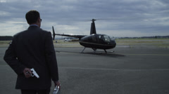 Businessman with gun forces helicopter pilot out of helicopter Stock Footage