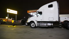 Night passing shot of tractor/trailers and fuel truck stop Stock Footage