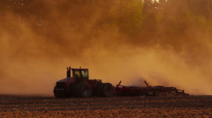 Tractor plowing field at sunset Stock Footage