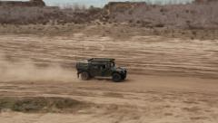 Military humvee passes left to right across desert floor Stock Footage