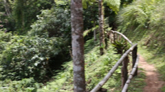 Pan from remote trail with fence to natural waterfall cascading off the hillside Stock Footage