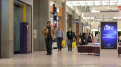 Mall visitors and woman in warm-up suit walking the mall for exercise Stock Footage