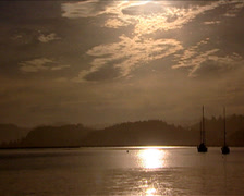 Long shot of a boat as it sails on the ocean during sunset - Knysna Harbour Stock Footage
