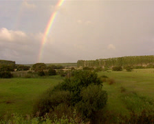 A full rainbow over a field Stock Footage