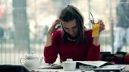 Stock Video Footage of pretty, young woman reading newspaper and drinking juice in the cafe