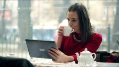 Young, beautiful woman using tablet and drinking tea in the cafe Stock Footage