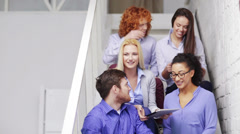 Team with tablet pc computer sitting on staircase Stock Footage