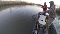 Two man fishing from a boat and catching fish - stock footage