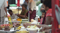 ASIA MARKET: Several sellers with food trays at street stall Stock Footage