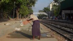 TRAIN LOCOMOTIVE: Worker sweeps train platform during repairs Stock Footage