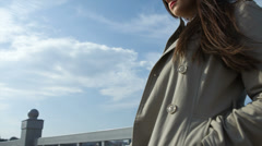 Young girl with phone against blue sky - stock footage