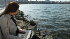 Businesswoman with laptop sitting on a beach in the sea coast Stock Footage