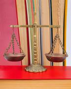 Scales of justice atop legal books Stock Photos