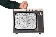 Fist hit broken TV - stock photo