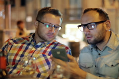 Two guys with smartphone talking in the restaurant at night, steadycam shot Stock Footage