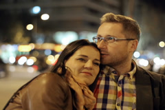 Couple in love sitting in night city, steadycam shot Stock Footage