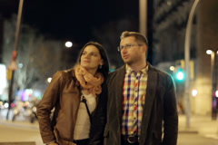 Young couple walking in night city, steadycam shot Stock Footage