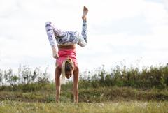 Agile young woman doing a handstand Stock Photos
