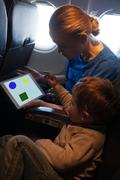 Young mother and son traveling on an aeroplane Stock Photos