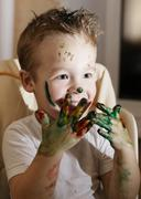 Excited little boy playing with finger paints Stock Photos