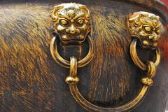 ancient bronze lions as a handle of vat - stock photo