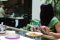 Young woman eating dinner at home, man bring pepper Stock Footage