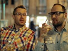 Two guys drinking beer and talking in the restaurant at night, steadycam shot Stock Footage