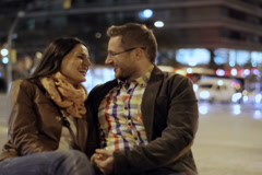 Couple in love sitting and talking in night city, steadycam shot Stock Footage