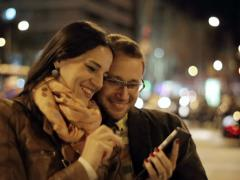 Couple taking photo with celphone in night city, steadycam shot Stock Footage