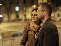 Young couple standing and looking around in night city, steadycam shot Stock Footage