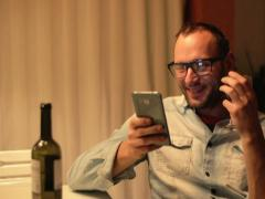 Young man with cellphone drinking red wine on the terrace in the evening Stock Footage