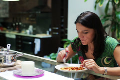 Young woman eating dinner at home Stock Footage