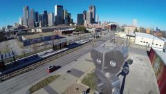 Aerial fly over Dallas train station w/  skyline and statue Stock Footage