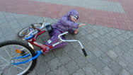 Stock Video Footage of child falling off his bicycle, then stands up and raises the bike