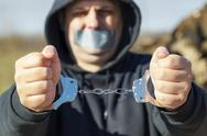 Stock Photo of Handcuffs on hands stretched forward
