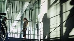 Businessman & woman casting a shadow meet & shake hands in modern city building - stock footage